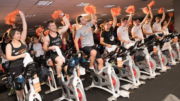 Enthusiastic participants cheer at a Cycle for Survival event.