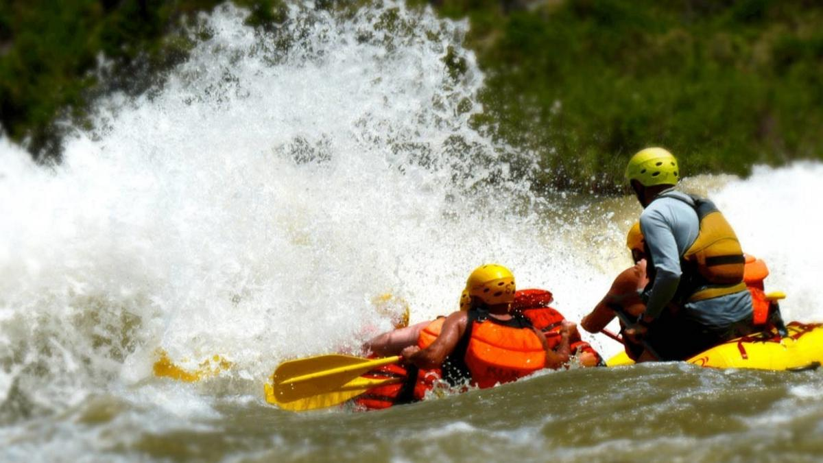 A commercial raft from a member of the Arkansas River Outfitters Association (AROA) drops a rapid at high water on the Arkansas River in Colorado.